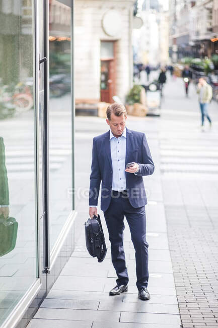 Mature businessman using smart phone while standing in city — Stock Photo