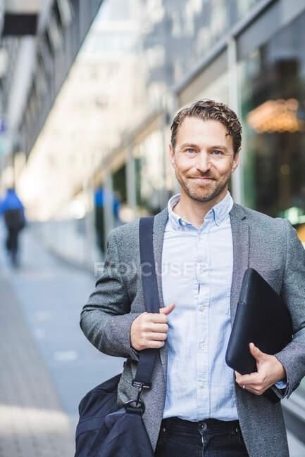 Портрет улыбающегося зрелого предпринимателя с сумкой, стоящего на улице — стоковое фото