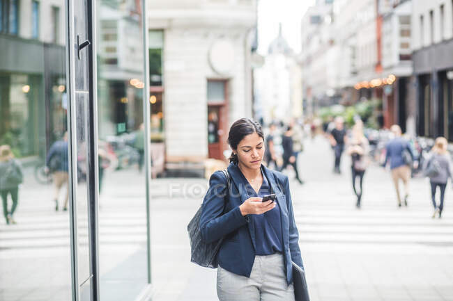 Businesswoman using phone while standing in city — Stock Photo
