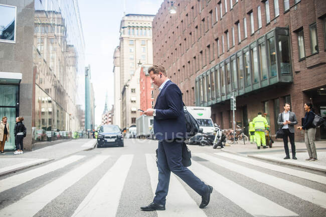 Mature businessman using phone while walking on zebra crossing in city — Stock Photo