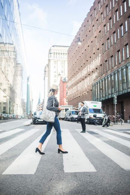 Geschäftsfrau überquert Straße in der Stadt — Stockfoto