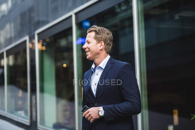 Smiling mature businessman with smart phone looking away while standing against office building — Stock Photo