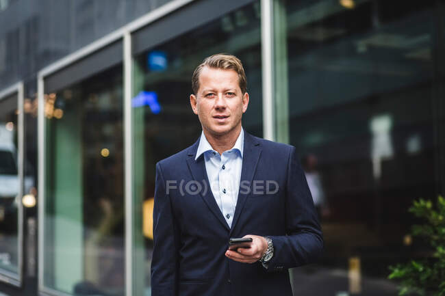 Portrait of mature businessman with smart phone standing against office building — Stock Photo