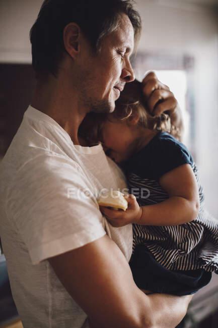 Зрелый отец с закрытыми глазами, держа дочь на руках — стоковое фото