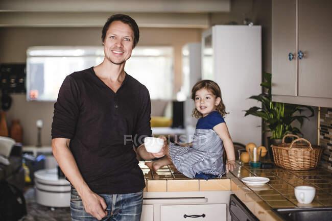Портрет улыбающегося зрелого мужчины с чашкой, пока дочь сидит на кухонном прилавке — стоковое фото