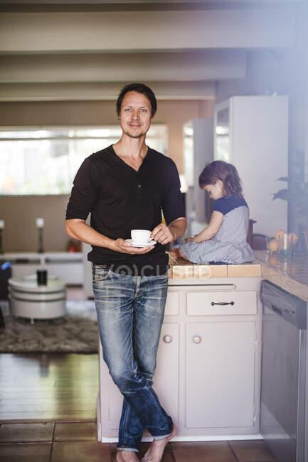 Портрет зрелого мужчины с чашкой, пока дочь сидит на кухонном прилавке — стоковое фото