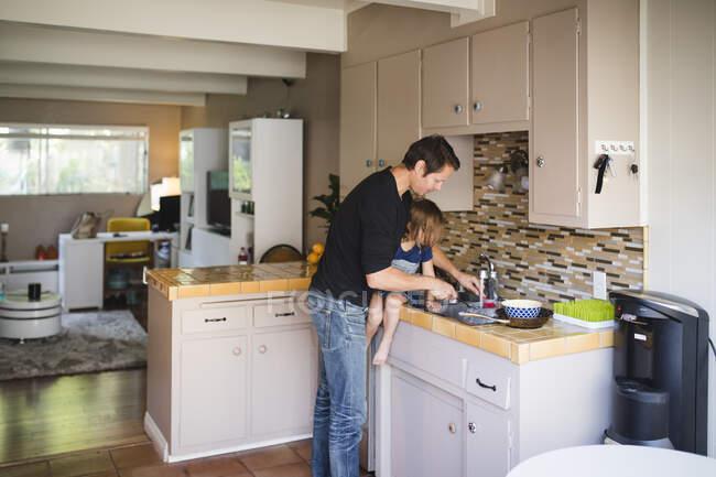 Отец моет кухню, а дочь сидит на кухонном прилавке — стоковое фото