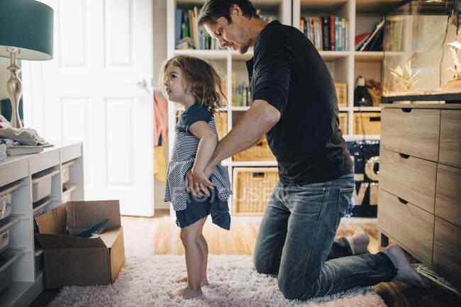 Padre vestire figlia in soggiorno — Foto stock