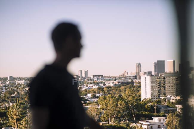 Вид сбоку зрелого мужчины, стоящего на балконе против города — стоковое фото