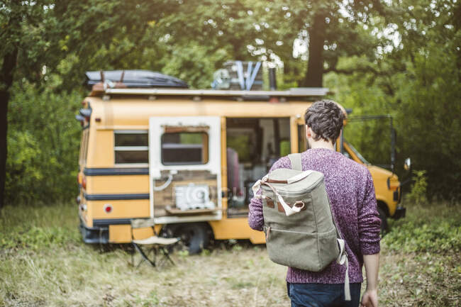 На задньому плані молодий чоловік під час відпочинку йде з рюкзаком до моторного будинку в лісі. — стокове фото