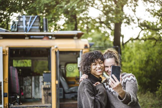 Donna che prende selfie con un amico contro carovana durante il campeggio nella foresta — Foto stock