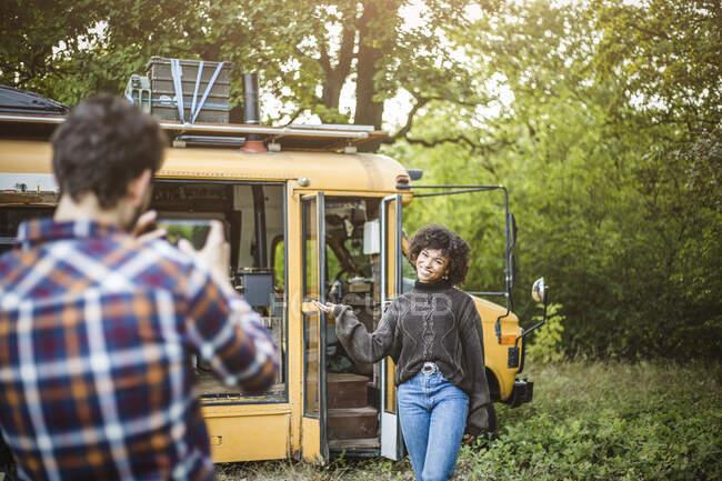 Felice giovane donna in posa contro carovana per il fidanzato durante il campeggio nella foresta — Foto stock