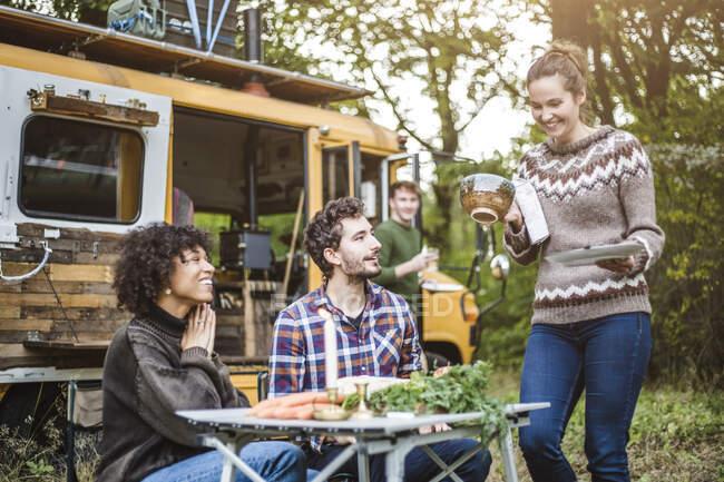 Donna sorridente che serve cibo per gli amici seduti a tavola contro la carovana durante il campeggio nella foresta — Foto stock