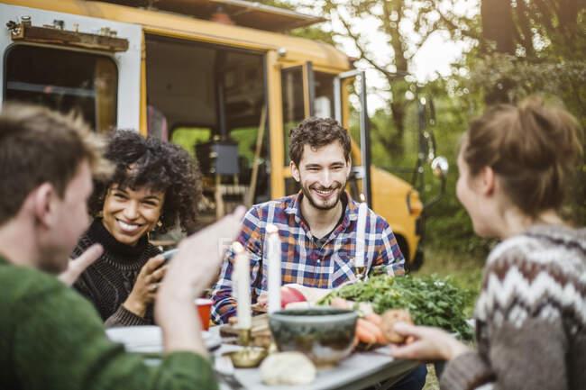 Amigos felizes desfrutando enquanto conversam na mesa durante o acampamento — Fotografia de Stock