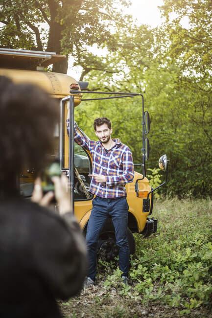 Giovane uomo in posa contro camper veicolo per la fidanzata durante il campeggio — Foto stock