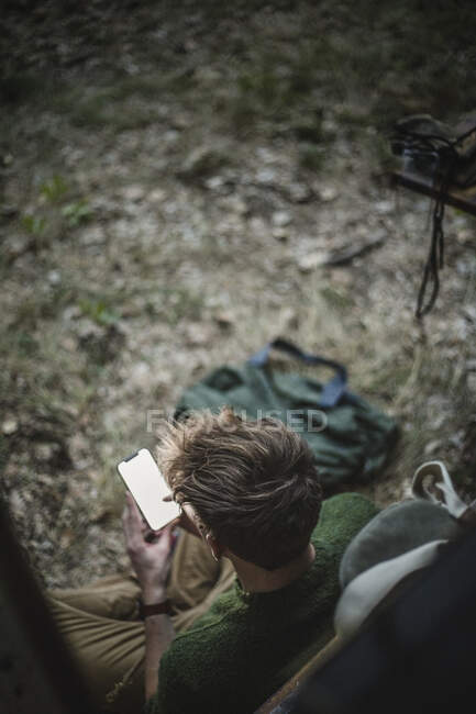 High angle view of man using smarphone against motor home during camping — стоковое фото