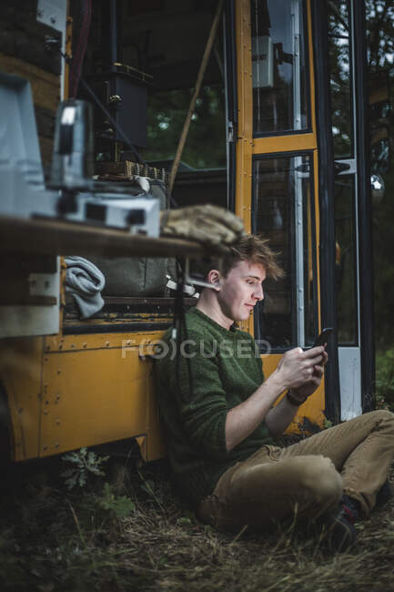 Full length side view of man sitting cross-legged while using smarphone against motor home during camping — стоковое фото