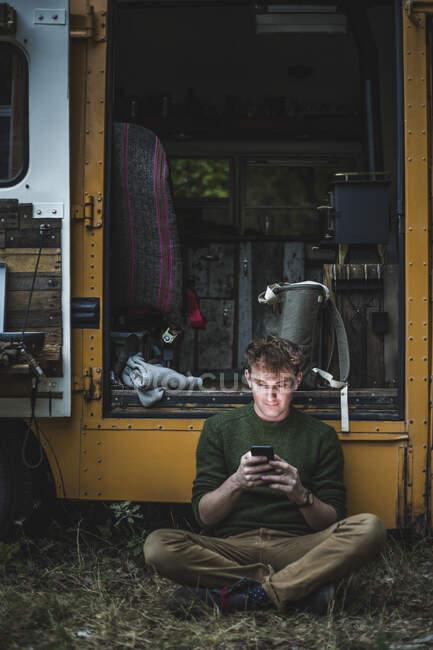 Lunghezza totale dell'uomo seduto a gambe incrociate durante l'utilizzo di smartphone contro camper durante il campeggio — Foto stock