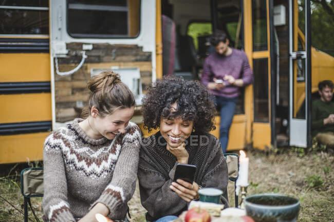 Amici femminili sorridenti che condividono smartphone mentre si siedono contro caravan durante il campeggio — Foto stock