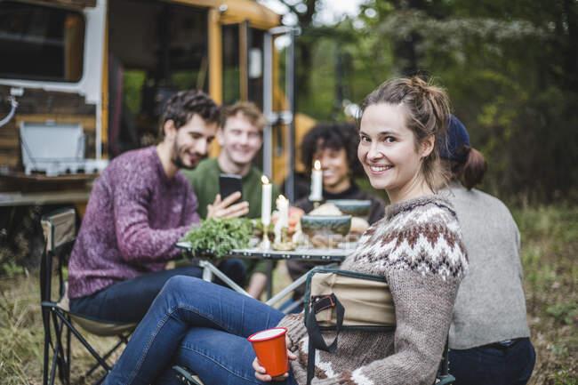 Porträt einer lächelnden blonden Frau, die im Wald beim Zelten mit Freunden am Tisch sitzt — Stockfoto