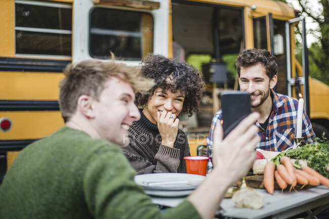 Smiling man showing smart phone to friends sitting at table against caravan — Stock Photo
