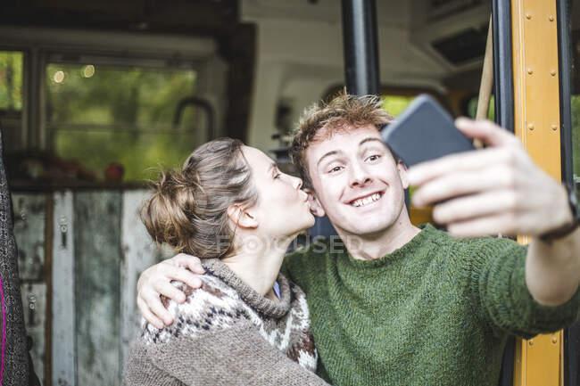 Uomo sorridente scattare selfie dal telefono cellulare mentre la donna lo bacia durante il campeggio — Foto stock