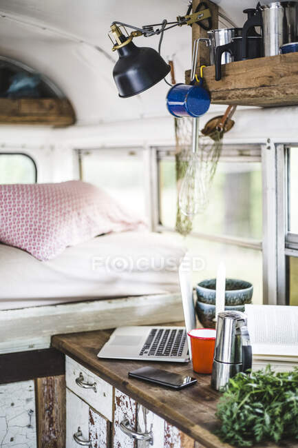 Technologies with food and drink on counter by bed in motor home — стоковое фото
