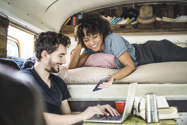 Felice giovane donna che mostra il telefono cellulare all'uomo seduto con il computer portatile nel camper — Foto stock