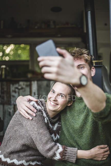 Uomo sorridente scattare selfie con la donna dal telefono cellulare durante il campeggio — Foto stock