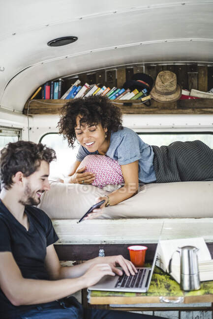 Smiling young woman showing smart phone to man sitting with laptop in motor home — Stock Photo
