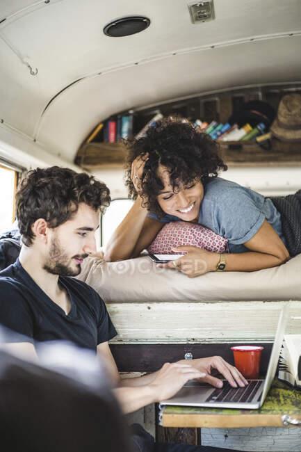 Sorrindo jovem deitado na cama enquanto olha para o homem usando laptop no motor home — Fotografia de Stock