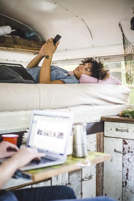 Giovane donna sdraiata sul letto mentre utilizza il telefono cellulare da uomo con laptop in roulotte — Foto stock