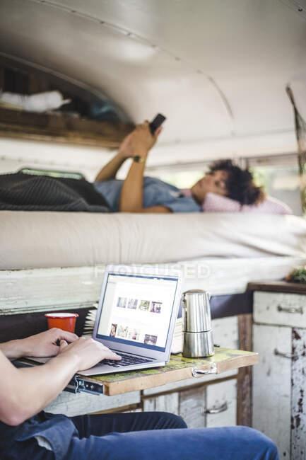 Sezione centrale dell'uomo utilizzando laptop da donna con telefono cellulare sdraiato sul letto in camper — Foto stock