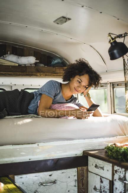 Giovane donna afro utilizzando smartphone mentre sdraiato sul letto nel camper — Foto stock