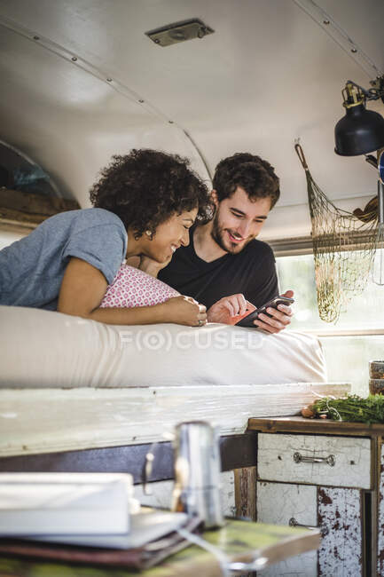 Smiling couple sharing mobile phone while lying on bed in caravan — Stock Photo