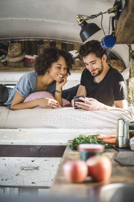 Smiling couple sharing smart phone while lying on bed in caravan — Stock Photo