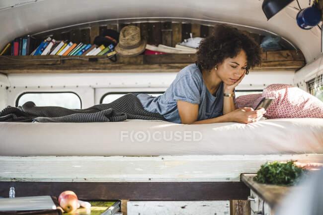 Giovane donna afro navigare attraverso il telefono cellulare mentre sdraiato sul letto in camper — Foto stock