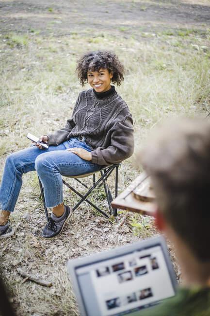 Sorridente giovane donna seduta sulla sedia mentre guarda amico maschio durante il campeggio nella foresta — Foto stock