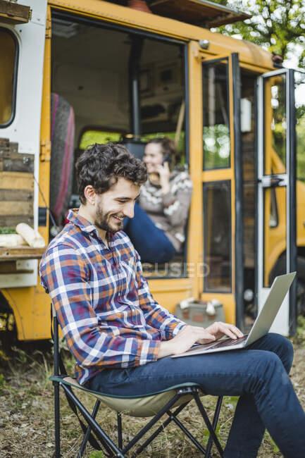 Sorridente giovane uomo utilizzando il computer portatile mentre seduto sulla sedia contro amico in camper veicolo — Foto stock