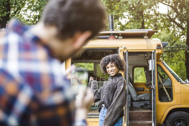 Allegro giovane donna in posa contro camper veicolo per fidanzato durante il campeggio — Foto stock