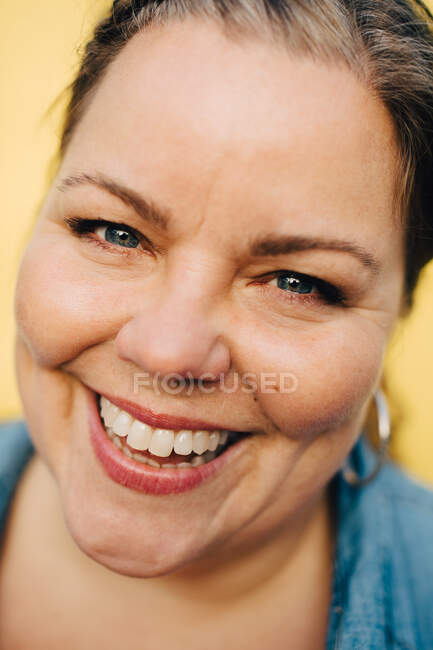 Close-up portrait of smiling mature woman against yellow background — Stock Photo
