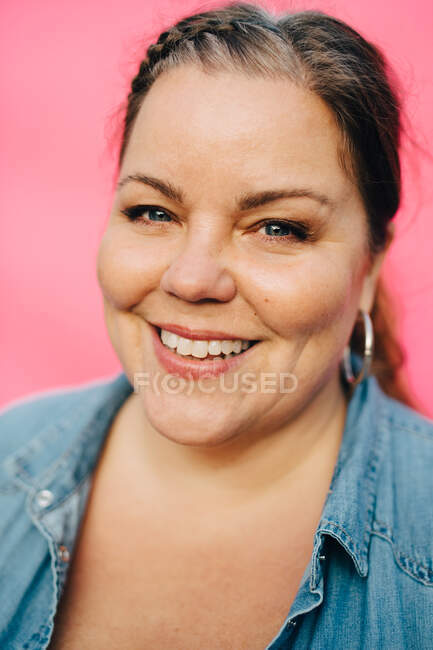 Портрет улыбающейся зрелой женщины на розовом фоне — стоковое фото