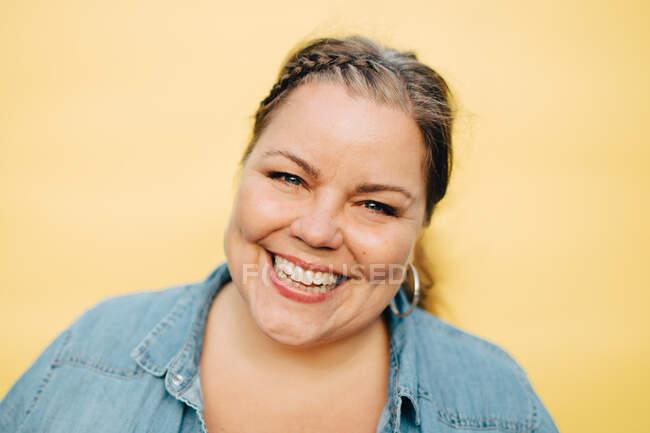 Retrato de mulher madura sorridente contra fundo amarelo — Fotografia de Stock