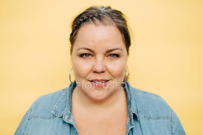 Retrato de mulher sorridente contra fundo amarelo — Fotografia de Stock