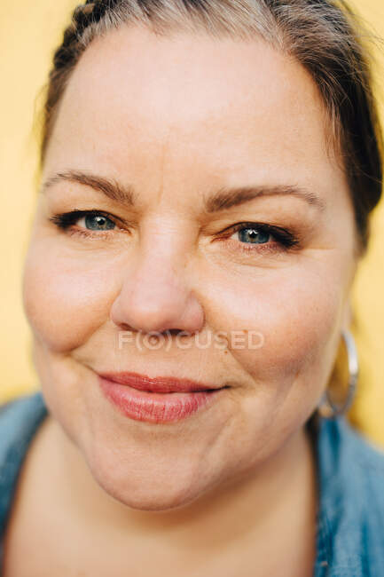 Close-up portrait of smiling woman against yellow background — Stock Photo