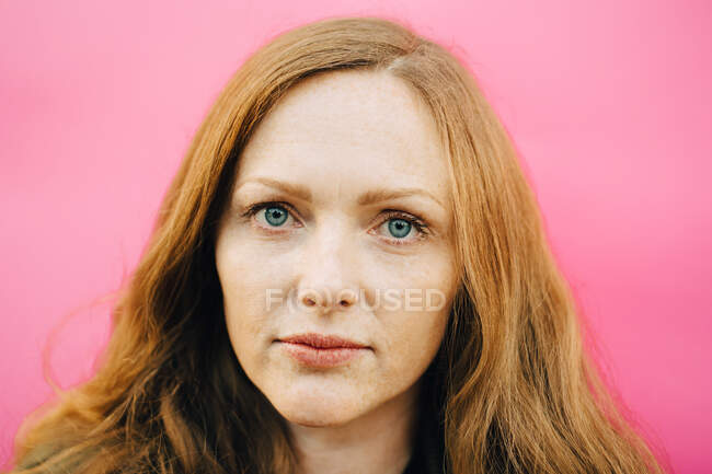 Portrait of mid adult woman against pink background — Stock Photo