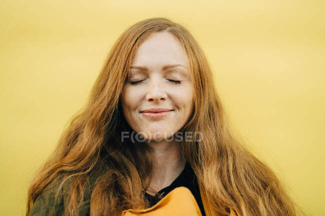 Smiling mid adult woman with eyes closed against yellow background — Stock Photo