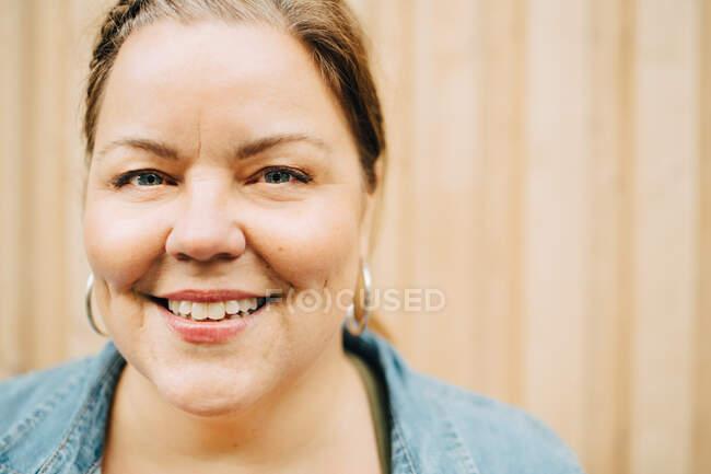 Портрет улыбающейся зрелой женщины у стены — стоковое фото