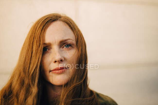 Портрет женщины с длинными волосами на стене — стоковое фото