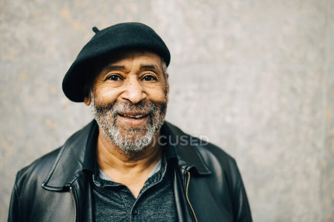 Portrait d'un homme âgé souriant contre un mur — Photo de stock